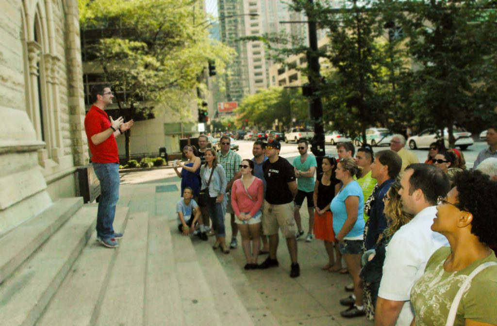 Crowd of tourists gathers outside a Chicago building to listen to a tour guide