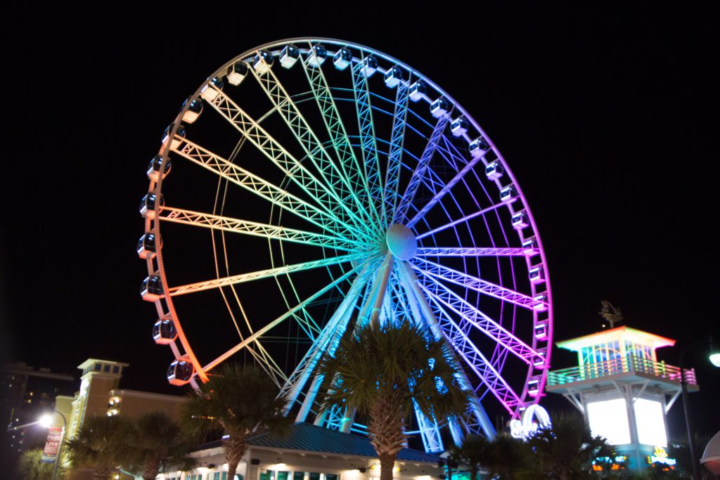 The Myrtle Beach Skywheel lit up with multiple colors at night.
