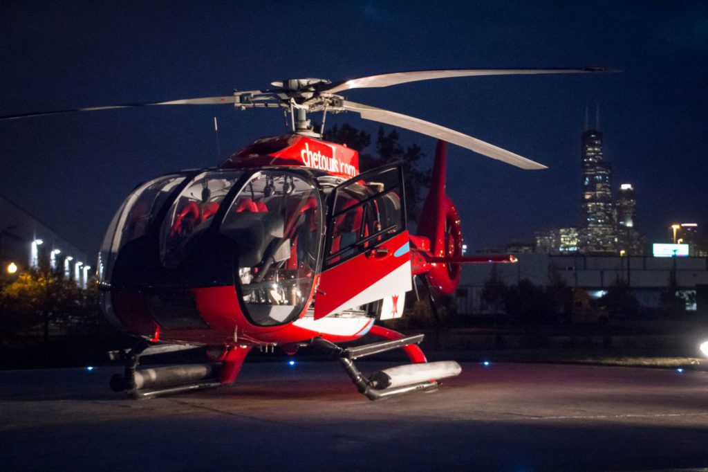 Chicago Helicopter on helipad at night with city skyline in the background