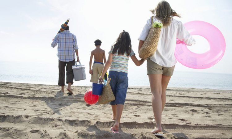 Family walks to beach with umbrella, towels, picnic basket, and beach toys in hand
