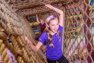 Girl climbs through ropes course