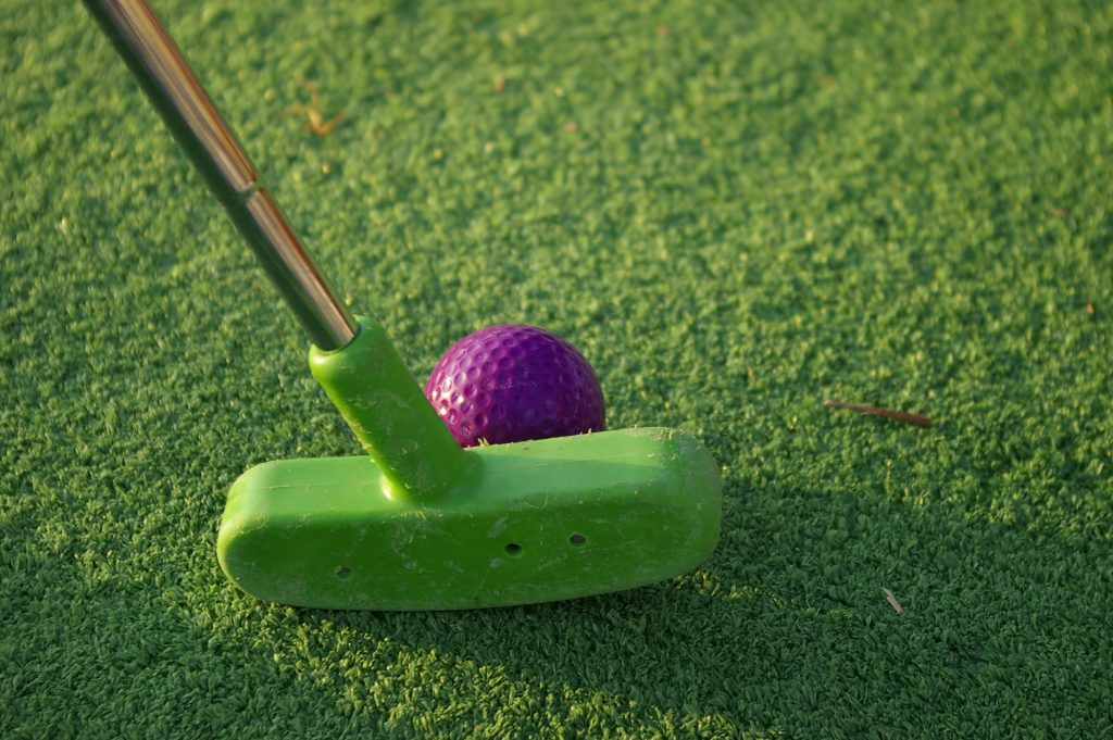 Green mini-golf club putting a purple golf ball