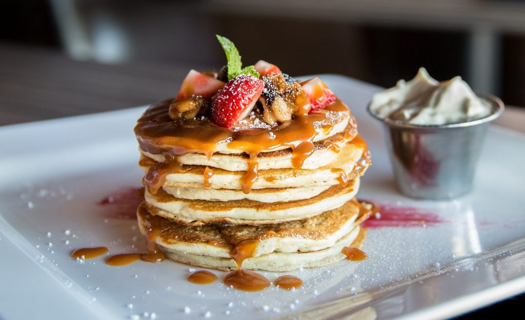 Pancakes topped with fruit and syrup