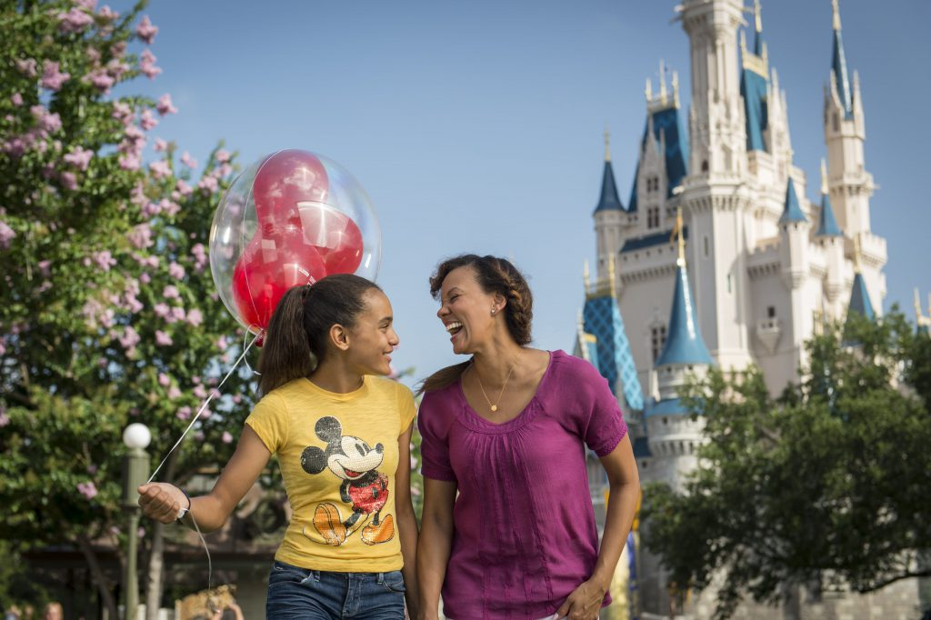 A woman and her daughter laugh in front of Cinderella's Castle. The girl is holding red Mickey Mouse balloons.