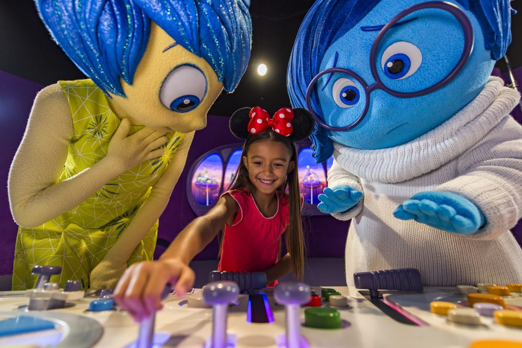 "A girl wearing Minnie Mouse ears engages with a Disney World exhibit while characters Joy and Sadness from Pixar's ""Inside Out"" look on"