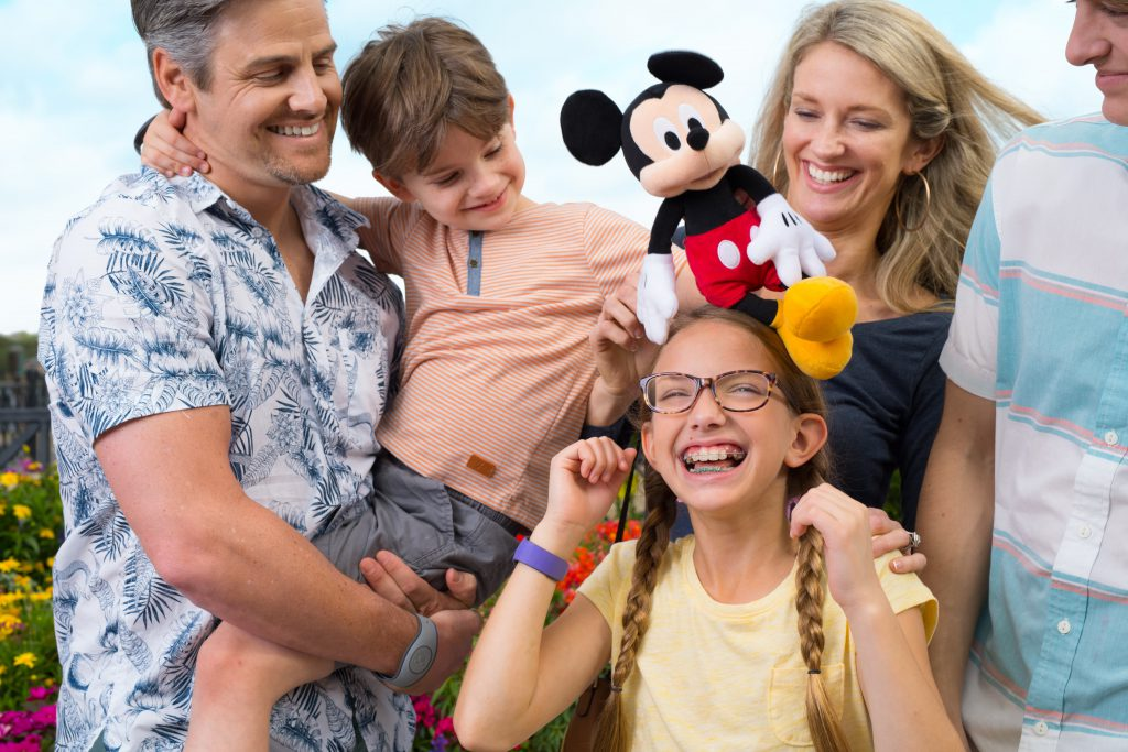 A family gathered together at Disney World with a Mickey Mouse stuffed toy