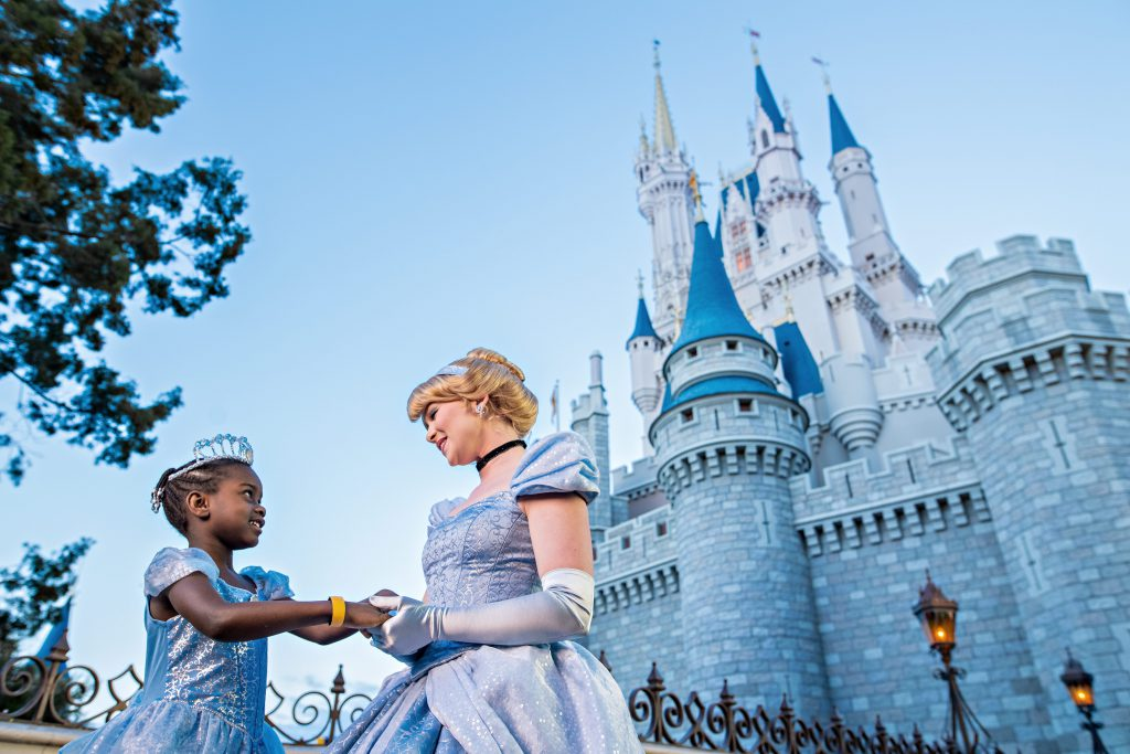 A little girl dressed as Cinderella meets the Princess in front of her castle on a sunny day