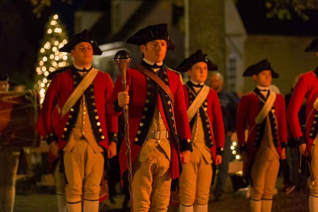 Colonial Williamsburg soldiers stand in front of a Christmas tree at night