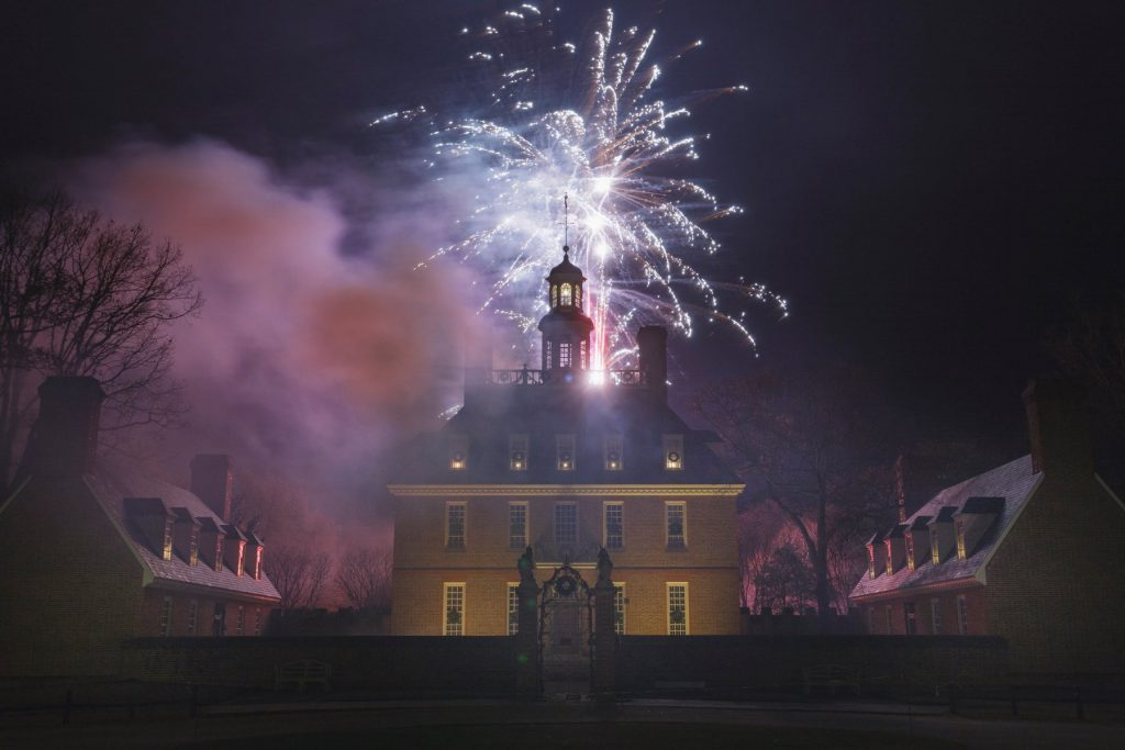 Red, white, and blue fireworks explode over a historic building at Colonial Williamsburg
