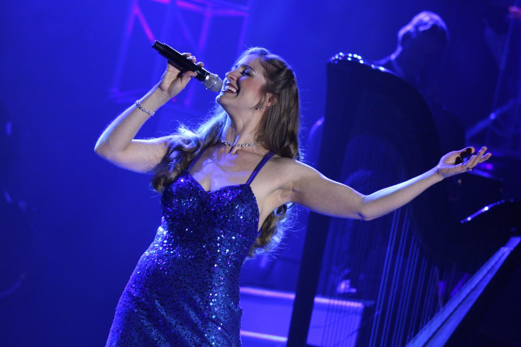 A woman in a blue dress sings into a microphone on stage
