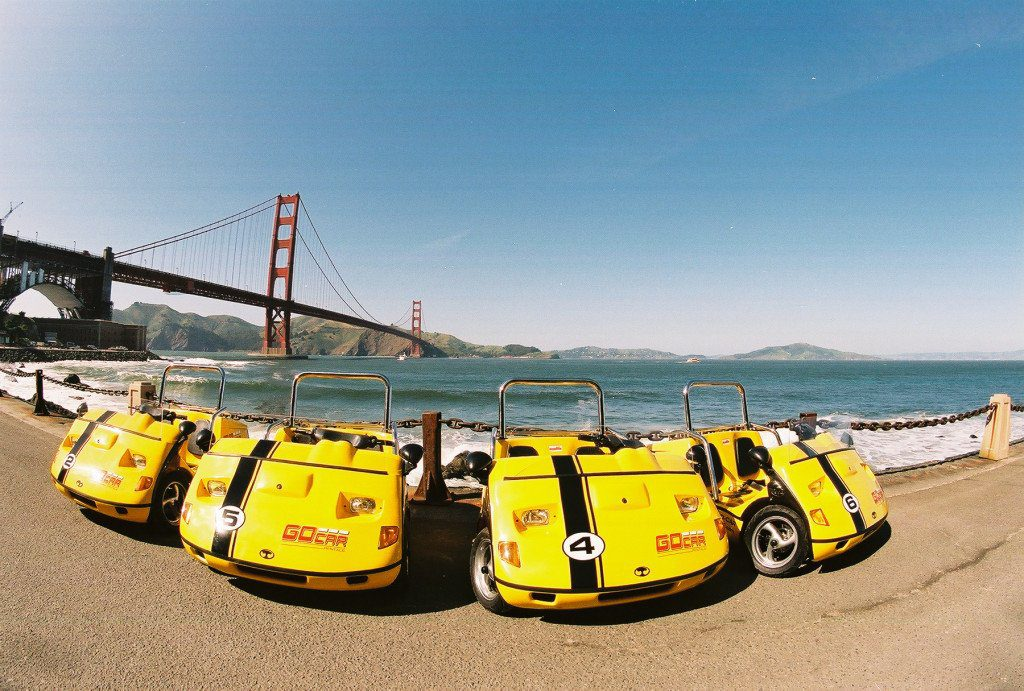 Yellow tiny Gocar vehicles lined up by the Golden Gate Bridge in San Francisco