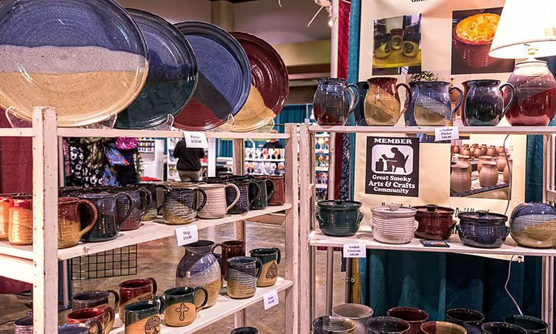 Handmade pottery and tableware is lined up on a display at the Great Smoky Arts & Crafts shows