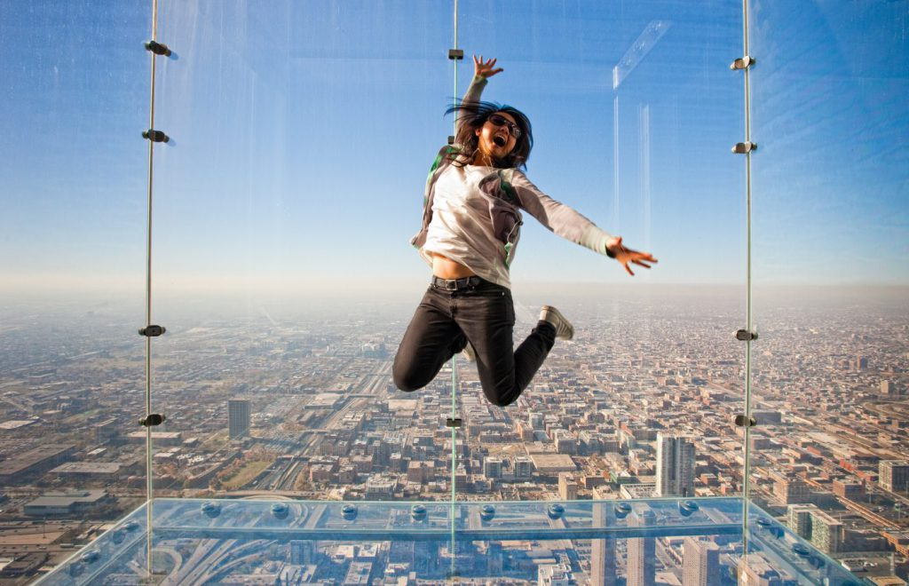Teenage girl jumps in a glass box at Skydeck Chicago in Chicago, IL