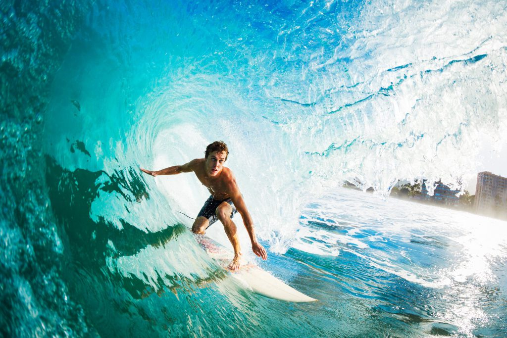 Man surfing on a turquoise wave in the ocean