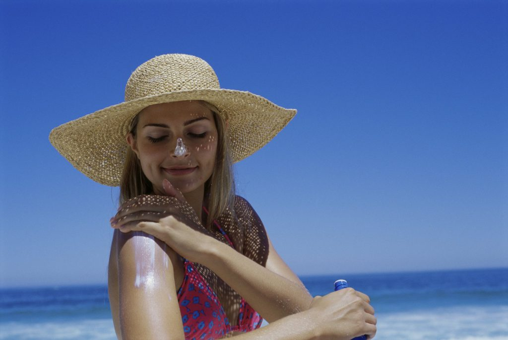 Woman in a pink bathing suit and straw sunhat applies sunscreen to her right shoulder at the beach