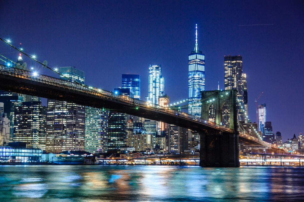 Lower Manhattan and the Brooklyn Bridge lit up at night over the bay