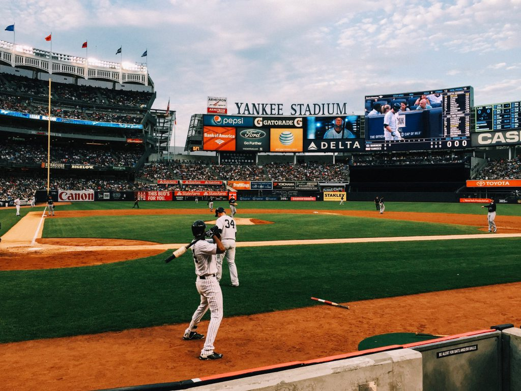 New York Yankees players warming up in Yankee Stadium on a clear day