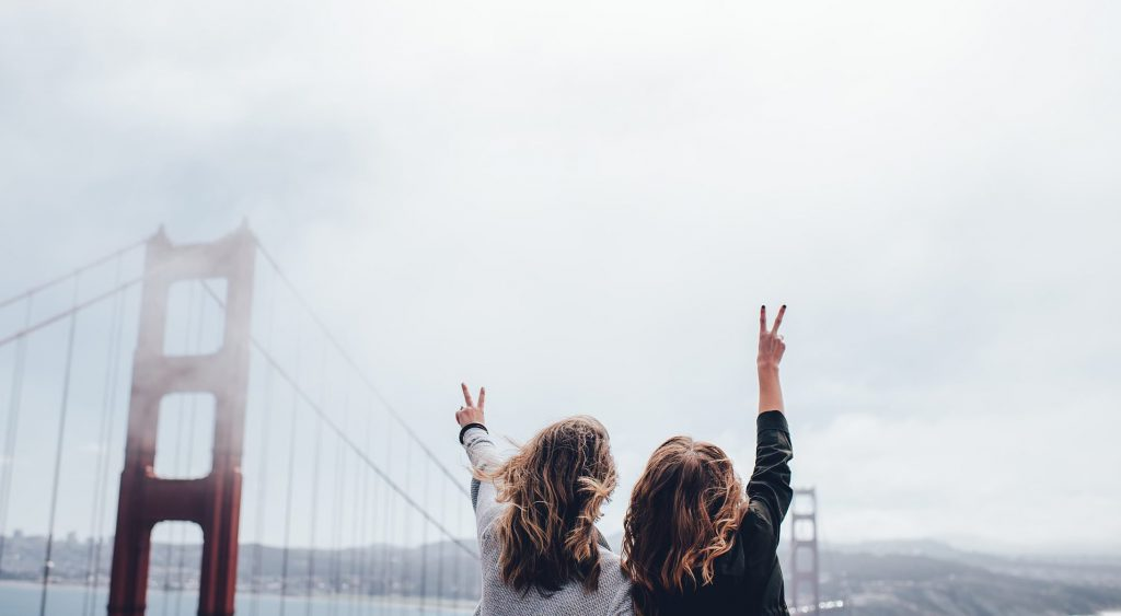 "Two teenagers raise their hands with ""peace signs"" on a cloudy day in front of the red Golden Gate Bridge"