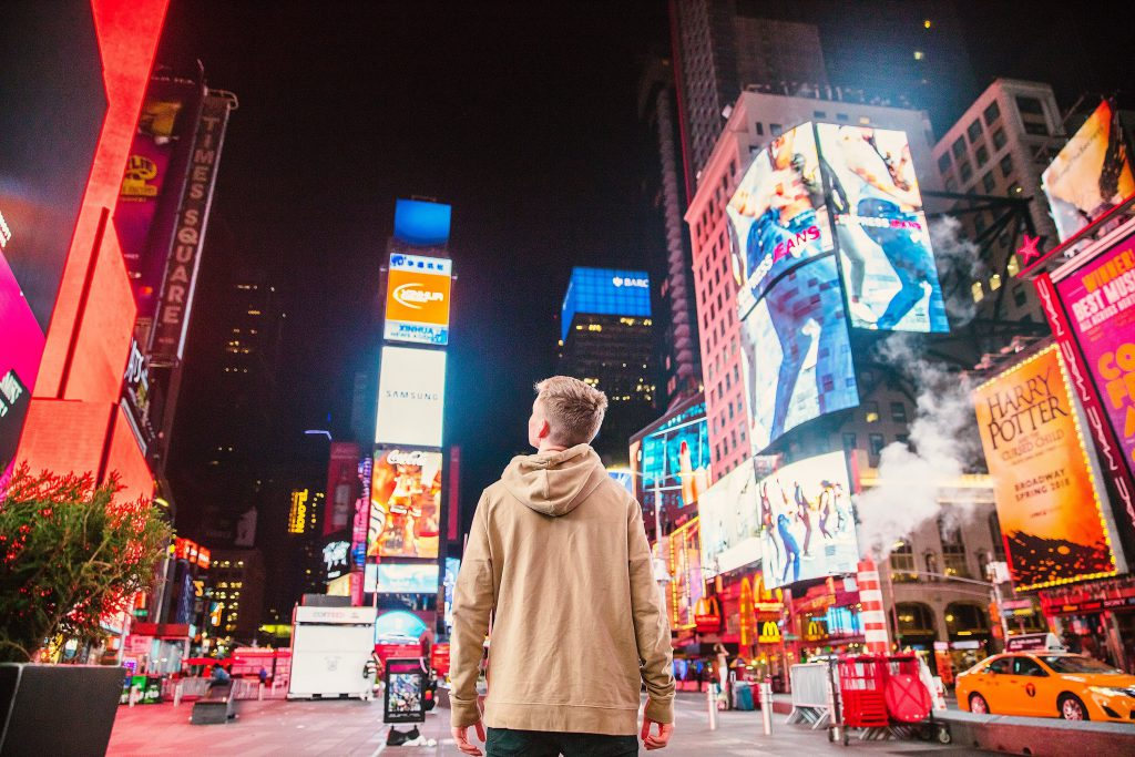 A teenage boy wearing a beige hoodie looks around at the neon lights and signs in Times Square, NYC