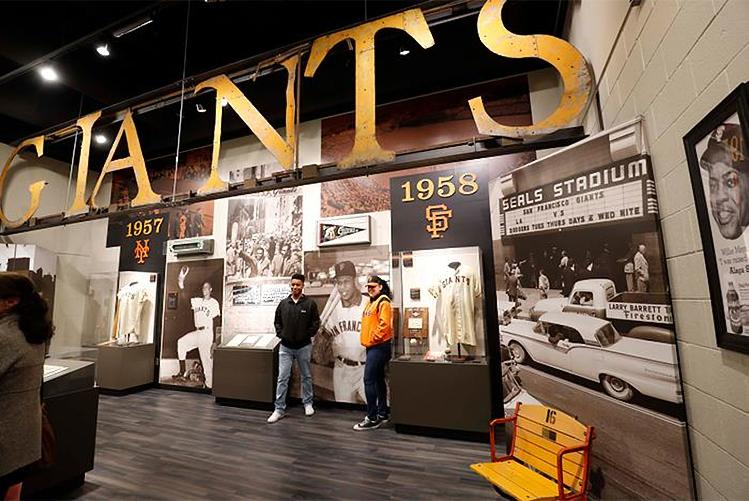 Two San Francisco Giants fans stand next to an exhibit detailing the history of the team