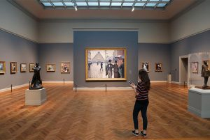An art gallery with wood floors and grey walls. Artwork hangs on the walls while a girl holding a cell phone stares at the art.