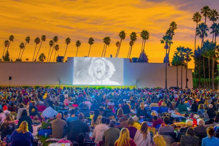 Fans sit in Hollywood Forever Cemetery watching Young Frankenstein at dusk