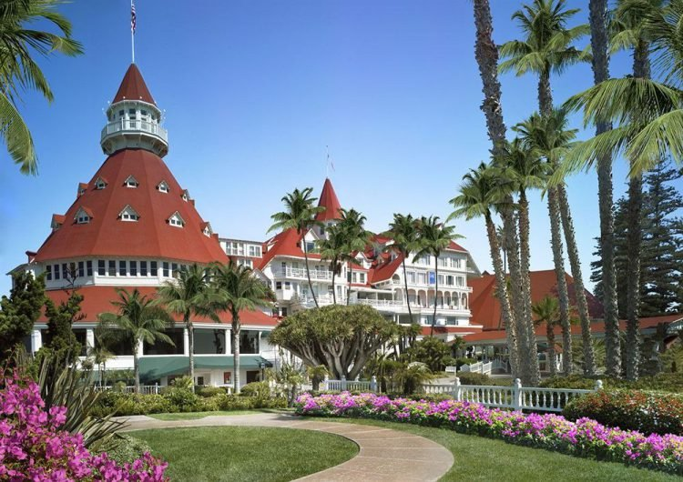 The exterior of the red and white Hotel del Coronado with palm trees lining the walkway to the hotel