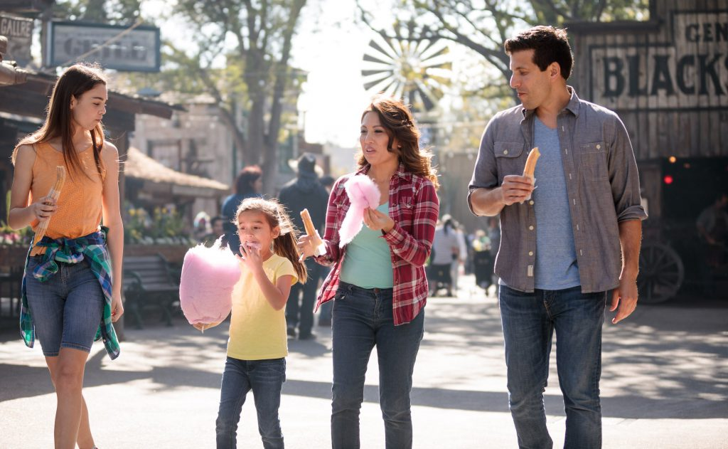 Family walking through Knott's Berry Farm with cotton candy and churros.
