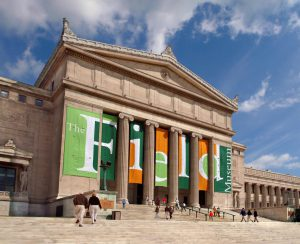 """The exterior of the Field Museum in Chicago. The word """"field"""" is spelled out on large vertical, orange and green banners"""