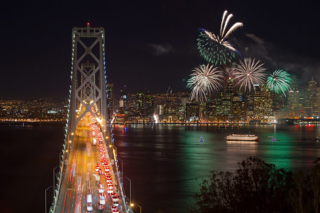 Fireworks explode over the San Francisco Bay with the Bay Bridge in View