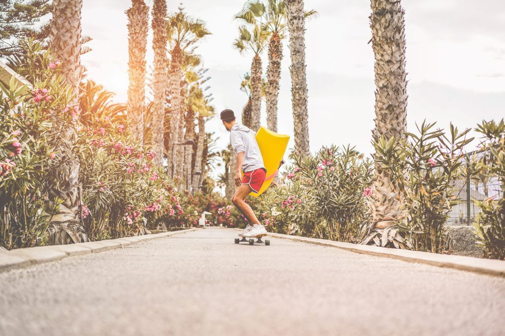 Man holds surfboard while skateboarding own palm tree lined streets in Los Angeles