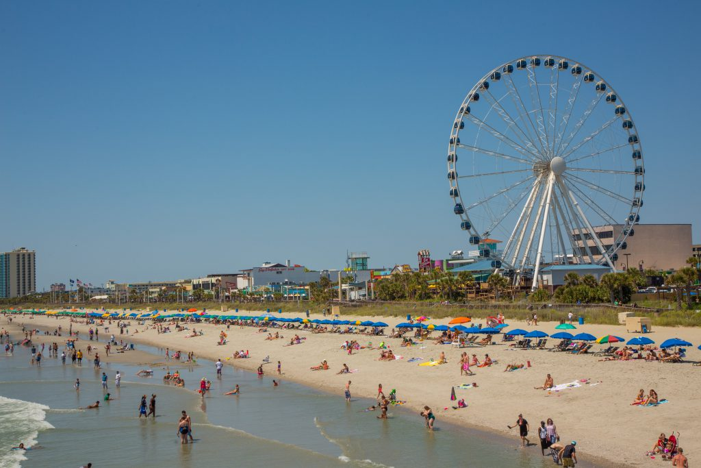 Myrtle Beach is filled with tourists on a sunny day and the Myrtle Beach skywheel is in the background