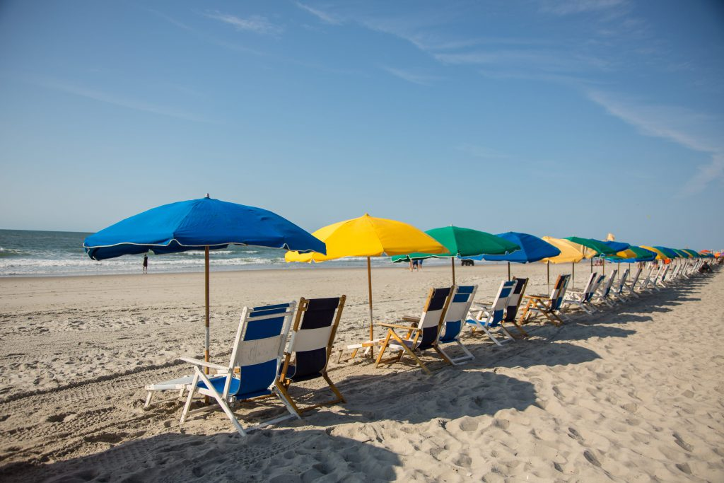 Empty blue, green, and yellow beach chairs and umbrellas sit in front of the Atlantic Ocean on Myrtle Beach