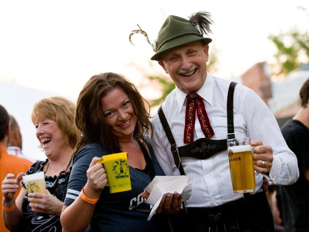 Oktoberfest participants dressed in traditional German attire toast with lager