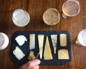 A board of assorted cheeses surrounded by glasses of beer