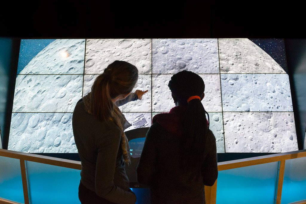 Two women look at a digital projection of the moon at the Adler Planetarium