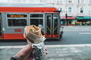 Person holds a burrito wrapped in tin foil in front of a bus