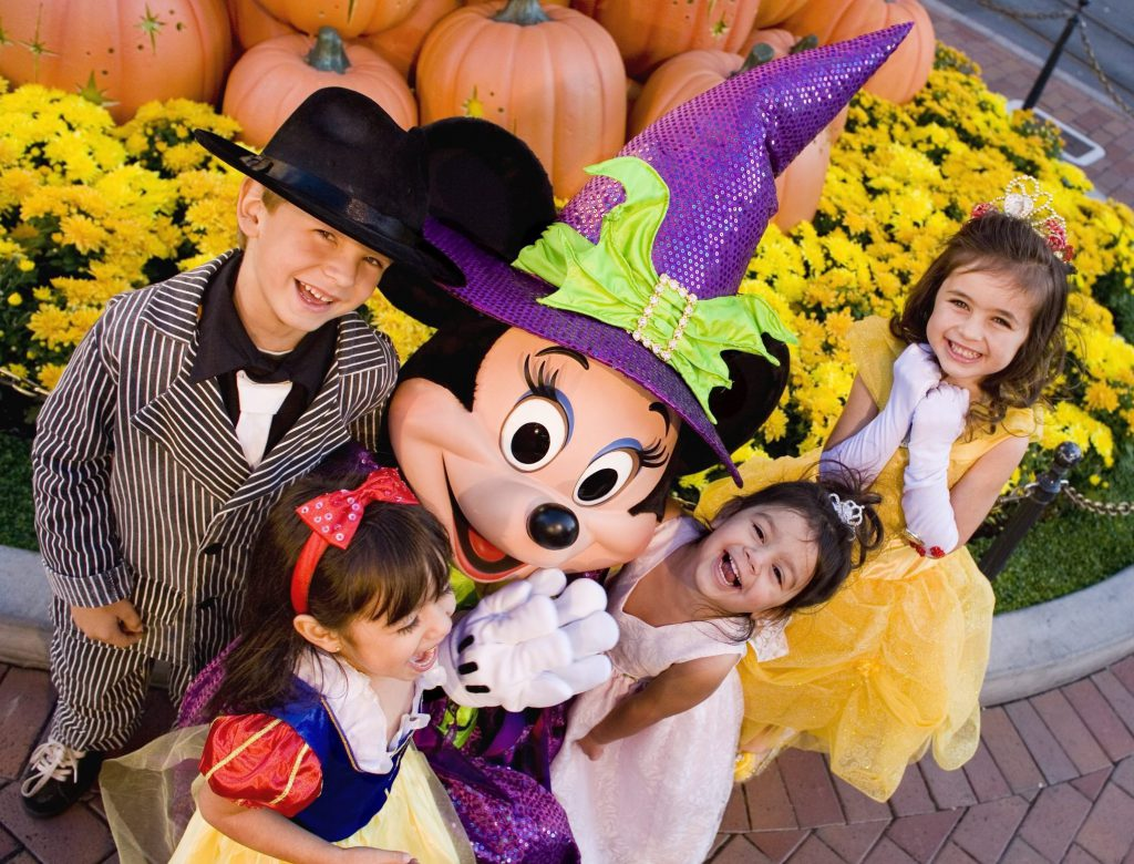 Minnie Mouse, dressed up for Halloween, hugs kids dressed as Snow White, Jack Skellington, and other Halloween characters