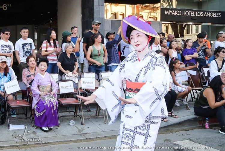 A woman in traditional Japanese clothing performs at the Nisei Week Festival