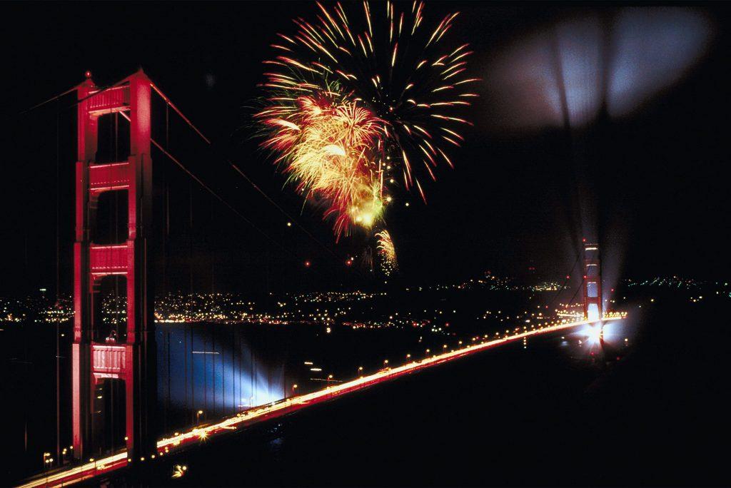 Orange fireworks explode over the Golden Gate Bridge at night