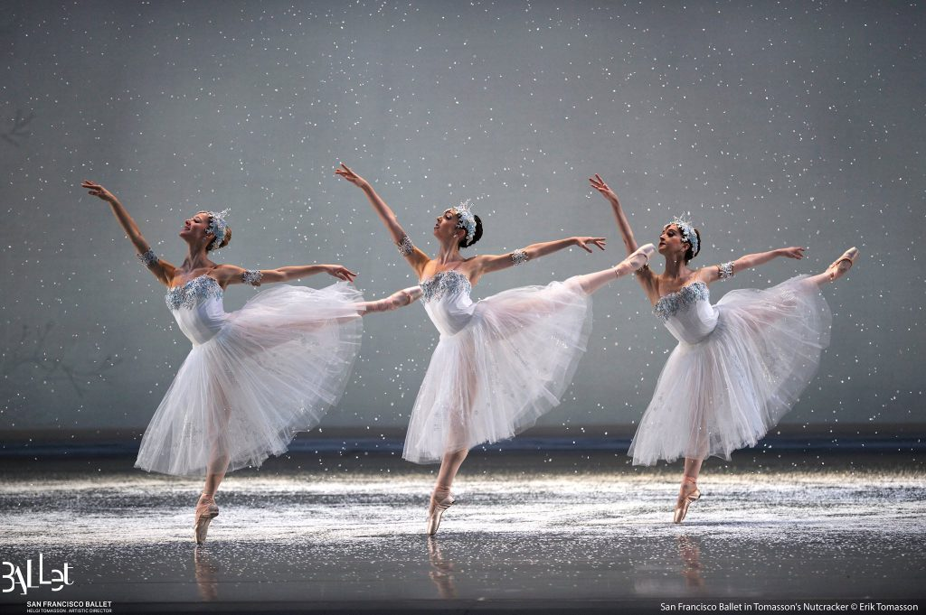 Three ballerinas in white perform the Nutcracker ballet on an empty stage