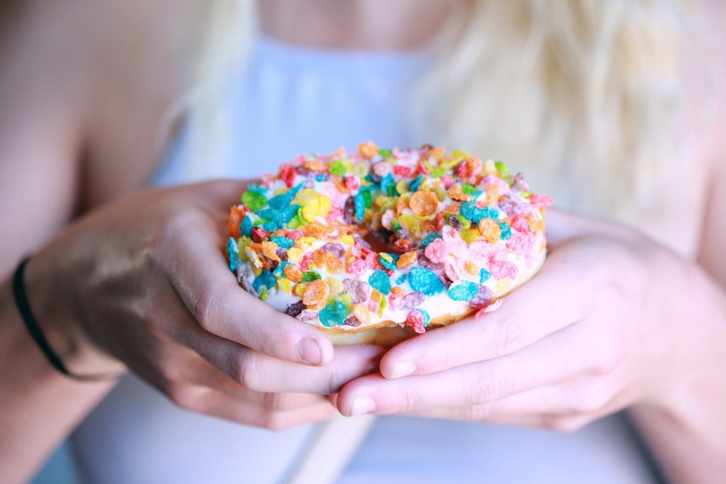 A blonde woman holding a pink donut with multi-colored sprinkles.