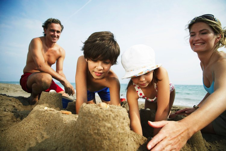Family building a sandcastle on the beach in Myrtle Beach, SC
