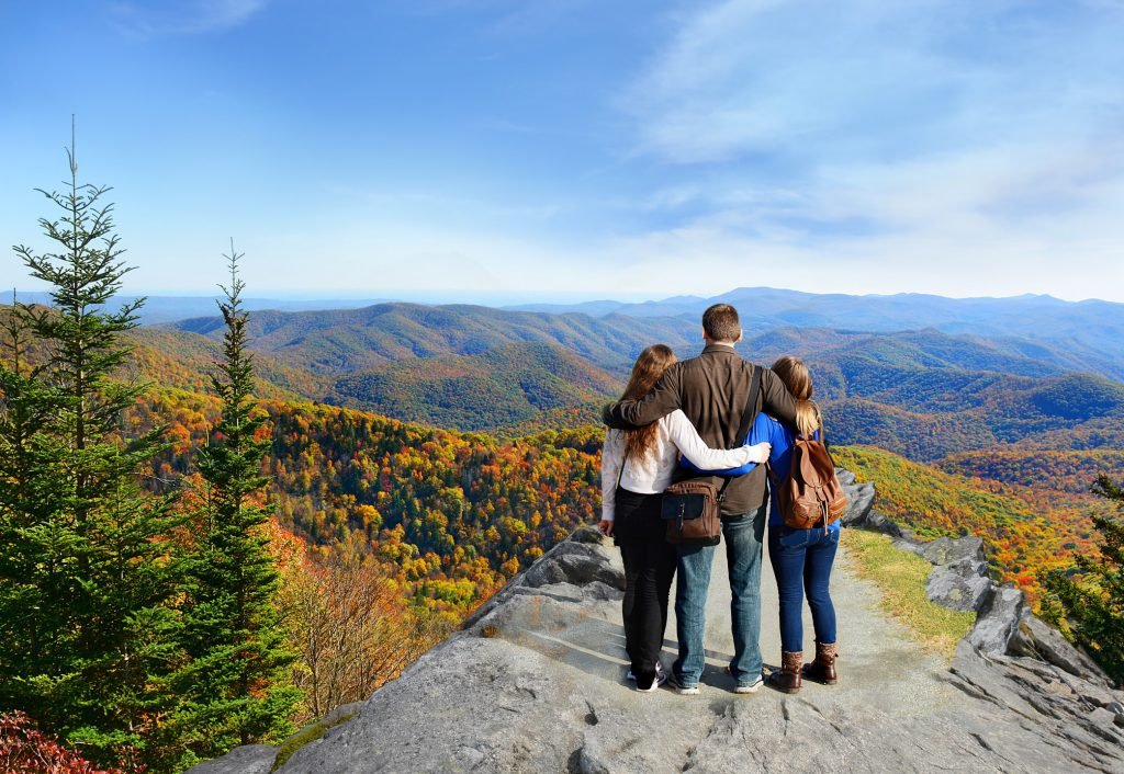 Family standing on top of the Smoky Mountains during the fall