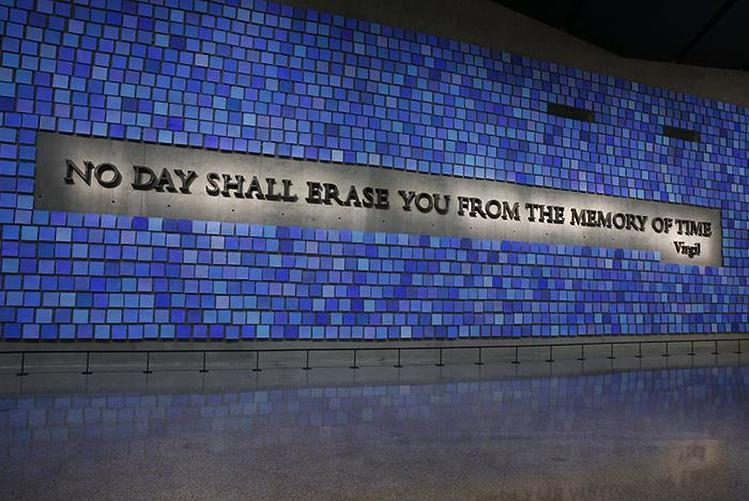 "A quote, ""No Day Shall Erase You From the Memory of Time,"" is etched in the wall surrounded by shades of blue, representing the color of the sky on 9/11."