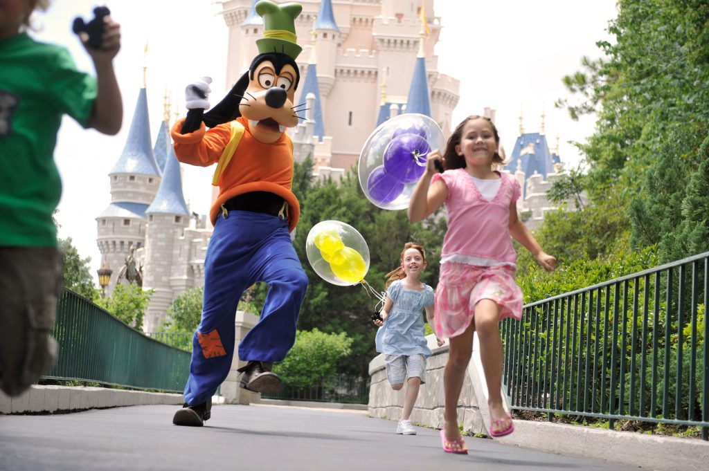 A little girl holds balloons and runs with Goofy at Disney's Magic Kingdom