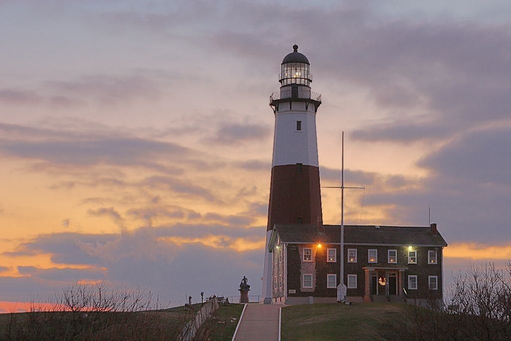 A man stands next to the Montauk Lighthouse at sunset