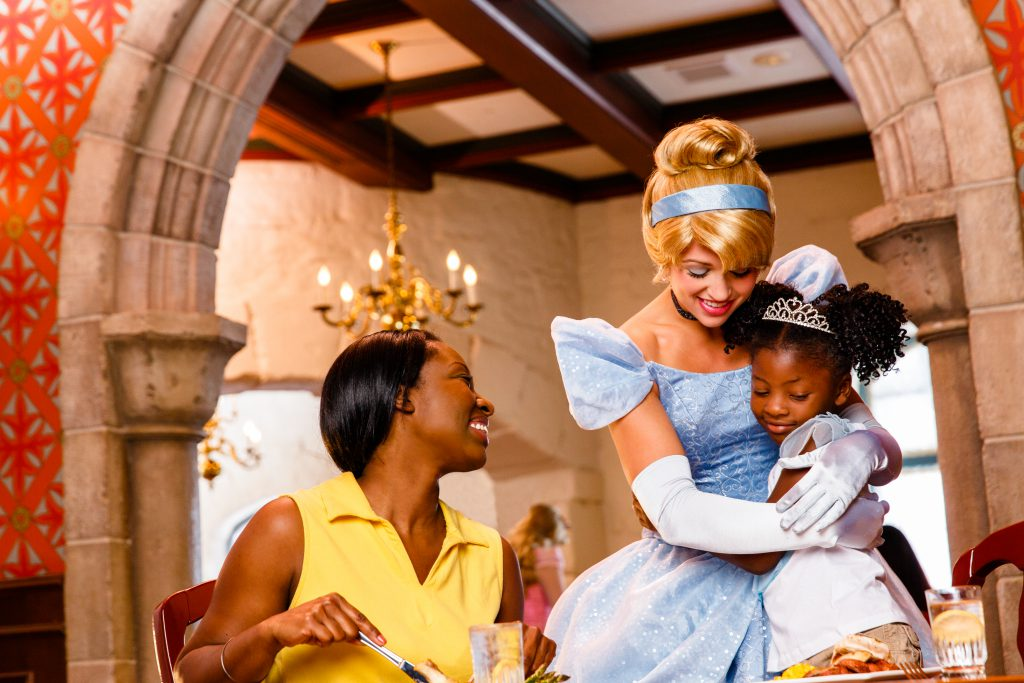 Cinderella hugs a little girl while her mother looks on at the Akershus Norway character dining experience