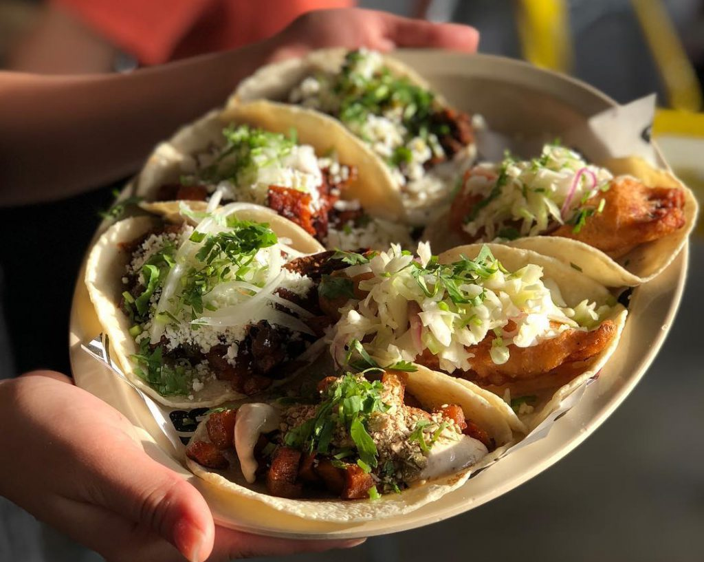 A woman holds a plate of tacos at Big Star in Chicago