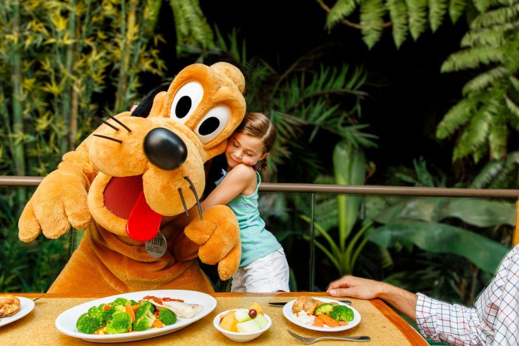 A little girl hugs Pluto at Epcot's Garden Grill